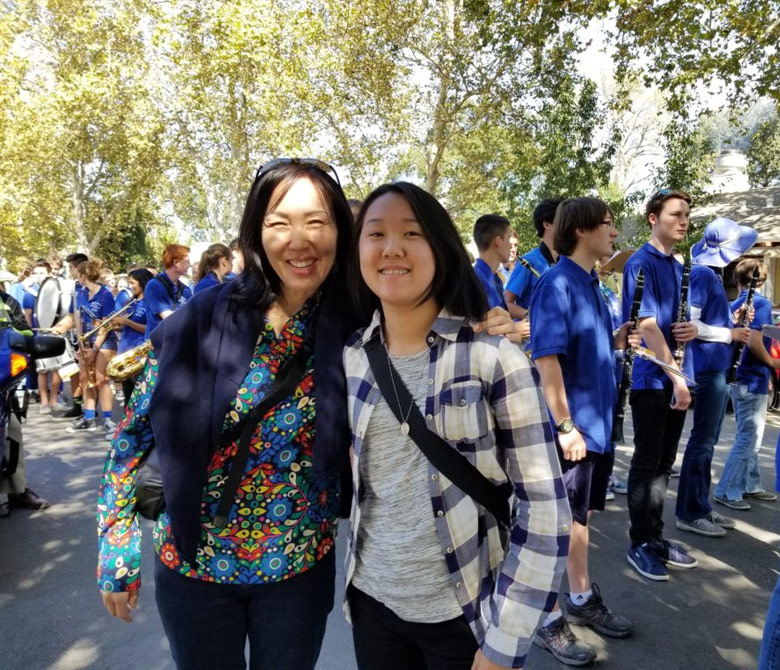 an image of two young Asian American women standing together for a photograph with lots of people behind them in the background