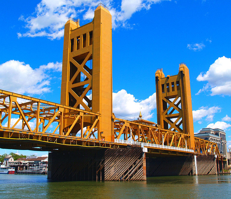 an image of the Tower Bridge in West Sacramento with a bright blue, slightly cloudy sky in the background